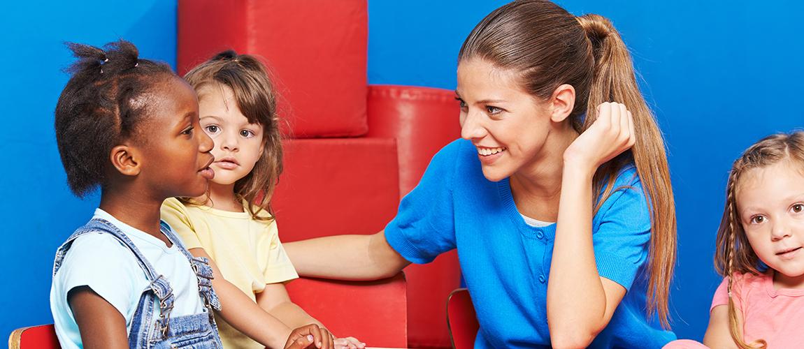 Kinder im Kindergarten machen Sprachförderung im Gesprächskreis mit Erzieherin
